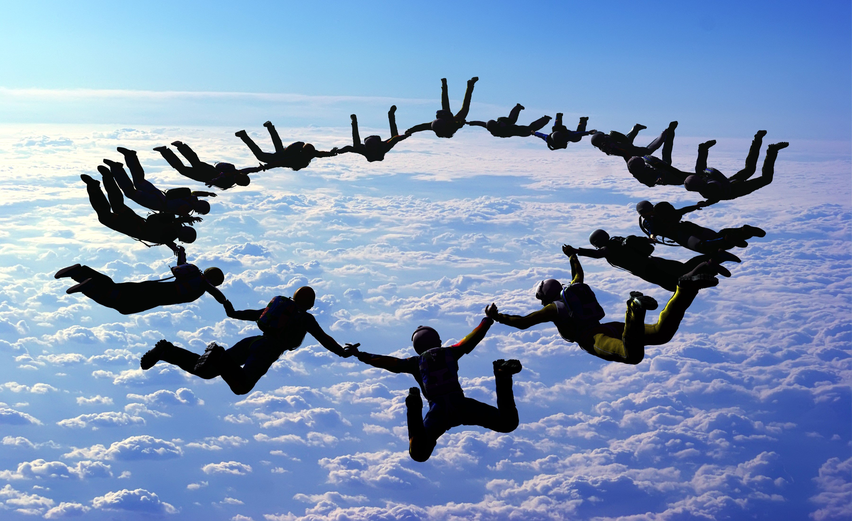 People parachute diving in open blue sky