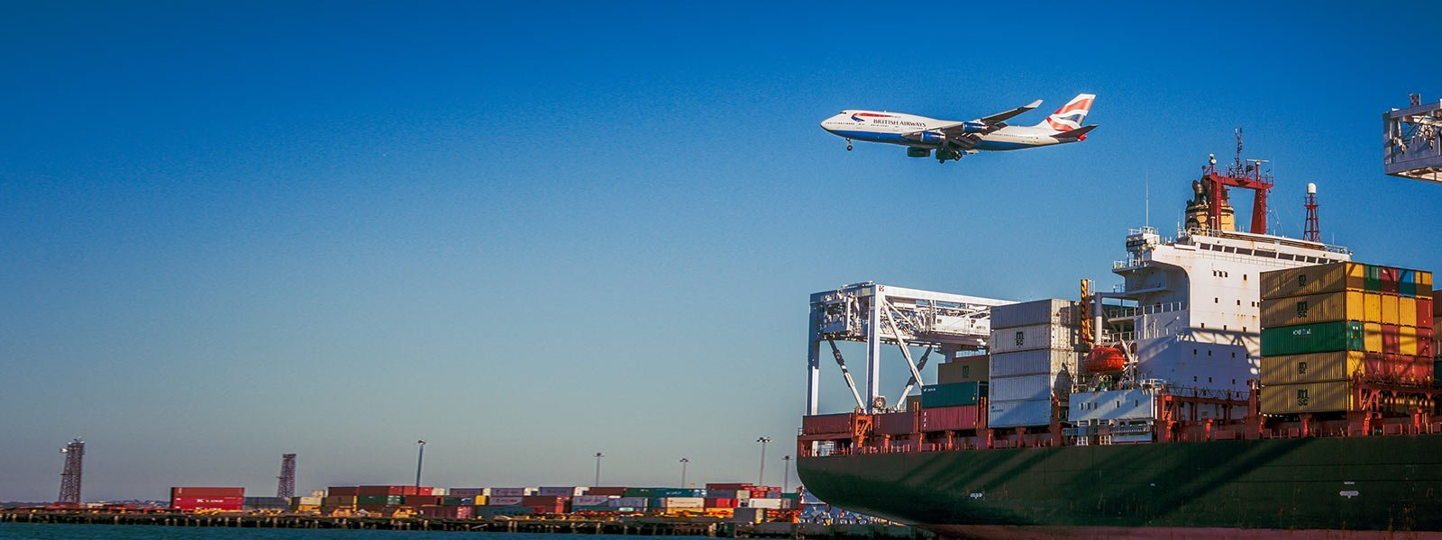 plane flying over container ship with containers in the background